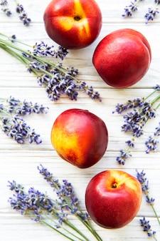 Nektarinen und blumen aus lavendel auf einer weißen holzoberfläche