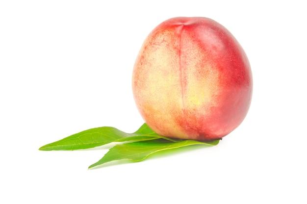 Nektarinenfrucht mit zwei blättern lokalisiert auf weißem ausschnitt.