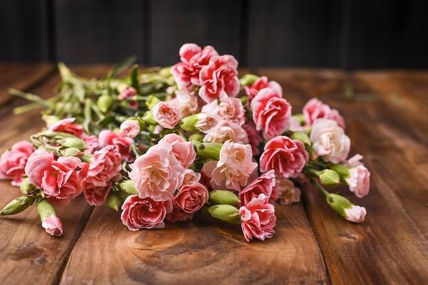 Nelke mit rosa und weißen blütenblättern auf einem holztisch. ein blumenstrauß als geschenk. altes foto. freier platz für text.