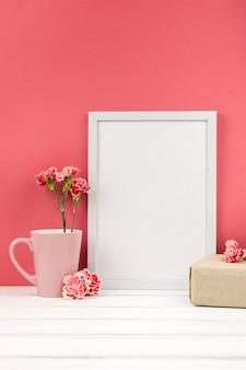 Nelkenblüten; geschenkbox; tasse und weißer leerer rahmen auf tabelle