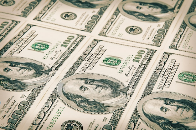 Nennwerte von einhundert dollar sind in einer reihe angeordnet. verarbeitung unter der antike. schräg betrachten.