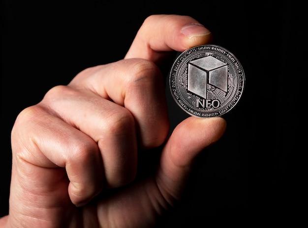 Neo glänzende silbermünze in männlicher hand über schwarzem hintergrund