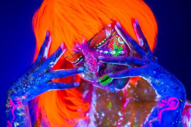 Neon frau tanzen. modemodellfrau im neonlicht, porträt des schönen modells mit fluoreszierendem make-up, kunst im uv, buntes make-up