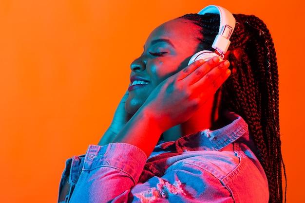 Neonporträt der jungen afrikanischen frau, die musik mit kopfhörern hört.