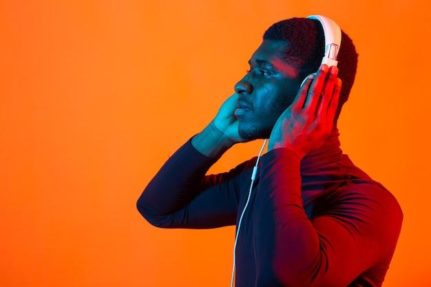 Neonporträt des jungen afrikanischen mannes, der musik mit kopfhörern hört.