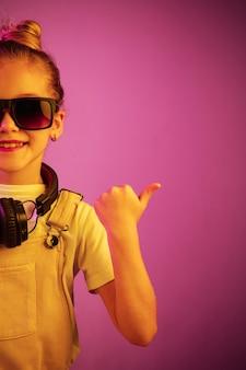 Neonporträt des jungen mädchens mit kopfhörern, die musik genießen. lebensstil junger menschen, menschliche gefühle, kindheit, glückskonzept.
