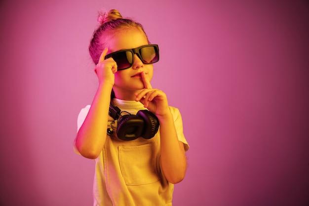 Neonporträt des jungen mädchens mit kopfhörern, die musik genießen und zur stille rufen.