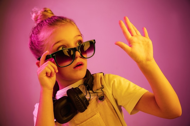Neonporträt des verängstigten jungen mädchens mit kopfhörern, die musik genießen.