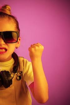 Neonporträt des wütenden jungen mädchens mit kopfhörern.
