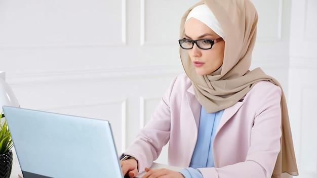 Nerd muslimische frau in beige hijab und anzug arbeitet an einem bachelor-abschlussprojekt, das auf laptop schreibt