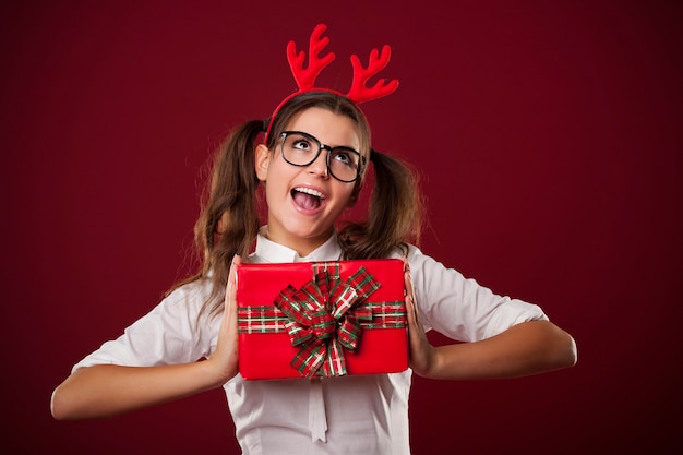 Nerdige frau, die rotes weihnachtsgeschenk hält
