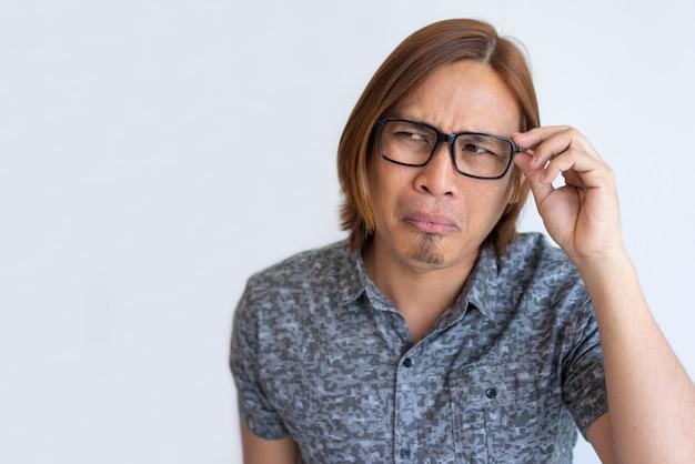 Nerdy asiatischer kerl, der an der kamera täuscht