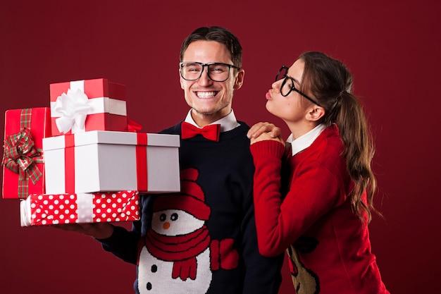Nerdy frau küsst ihren freund in der weihnachtszeit