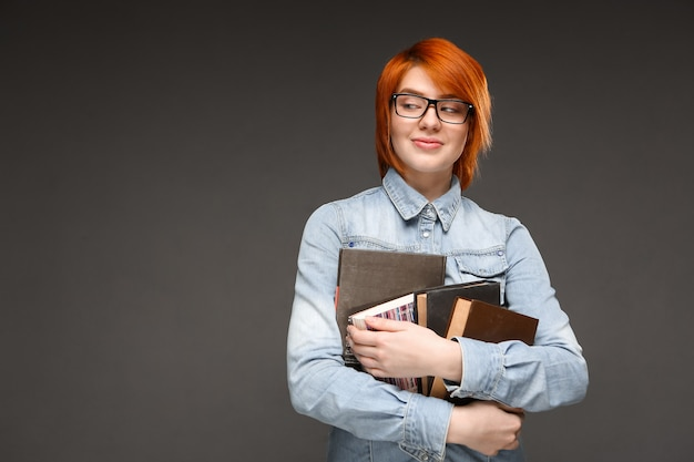 Nerdy rothaarige studentin tragen bücher