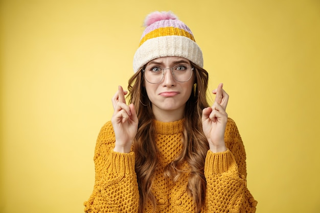 Nervös, unsicher, unsicher, süßes nerd-mädchen, universitätsstudentin mit brille, schmollend, weinen, jammern, besorgt, gekreuzte finger, viel glück, betend, wird ein traum wahr, der intensiv gelber hintergrund steht