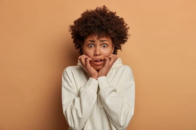 Nervöse ängstliche frau starrt mit verängstigtem sprachlosem ausdruck, beißt fingernägel, fühlt sich gestört und unsicher, erkennt gefahr, macht sich sorgen um etwas