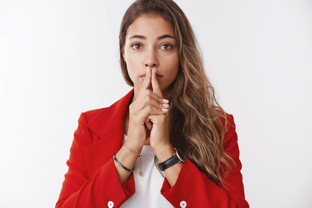 Nervöse, attraktive, ernst aussehende junge geschäftsfrau, die auf wichtige ergebnisse wartet, besorgt, die handflächen zusammenhalten und die lippen berühren, die ängstlich kamera suchen und hoffentlich gute nachrichten erwarten