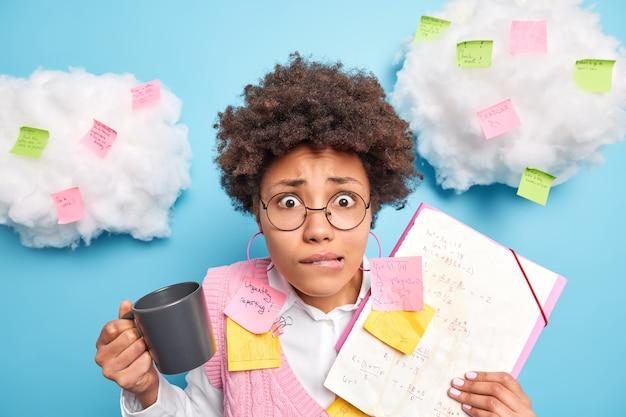 Nervöse besorgte studentin beißt sich auf die lippen, nachdem sie die abschlussprüfung in mathematik bestanden hat. sie hält ein blatt papier mit formeln und bunten aufklebern um getränke. kaffee bereitet sich auf die prüfungssitzung vor