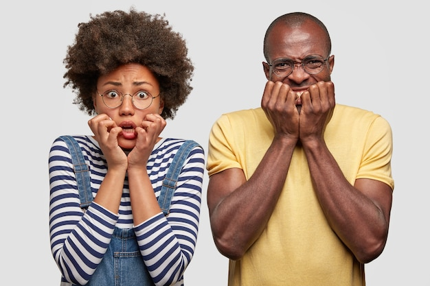 Nervöse dunkelhäutige frauen und männer sehen ängstlich aus, halten die hände in der nähe des mundes, bemerken etwas schreckliches, lässig gekleidet, isoliert über der weißen wand. überraschtes familienpaar sieht nervös aus