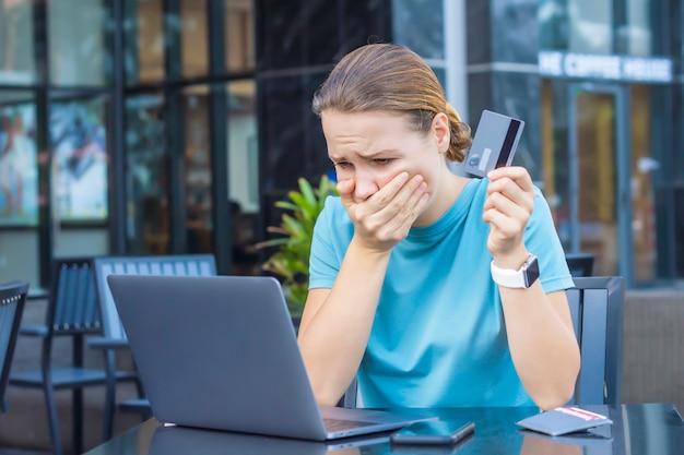 Nervöse entsetzte verwirrte junge frau, betonte besorgte dame, die probleme mit dem bezahlen, dem online-kauf, den zahlungen mit der blockierten bankkarte, dem betrachten des bildschirms, des laptop-monitors hat. internetbetrug