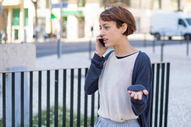 Nervöse frau, die auf smartphone geht und spricht