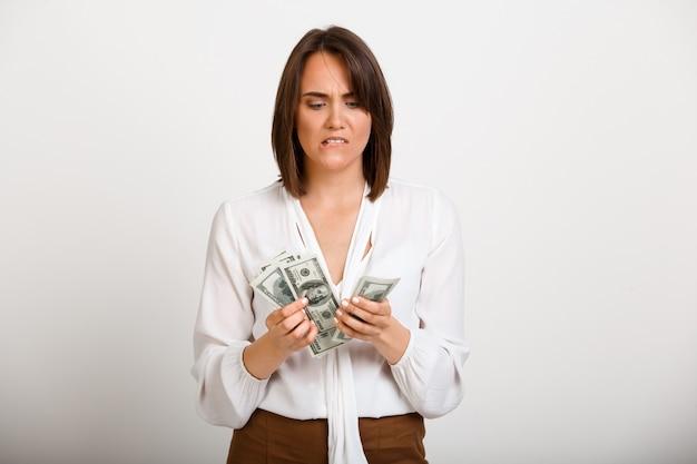 Nervöse frau, die geld zählt, bargeld fehlt