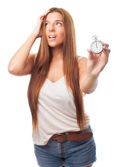 Nervöse frau mit langen haaren hält stoppuhr