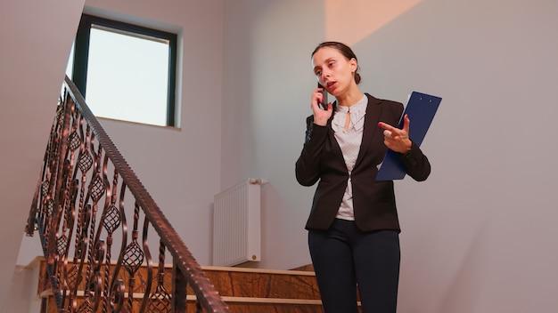 Nervöse geschäftsfrau, die auf dem smartphone mit dem unternehmensleiter spricht, der auf der treppe im finanzgebäude steht und überstunden macht. gruppe professioneller geschäftsleute, die an einem modernen finanzarbeitsplatz arbeiten.