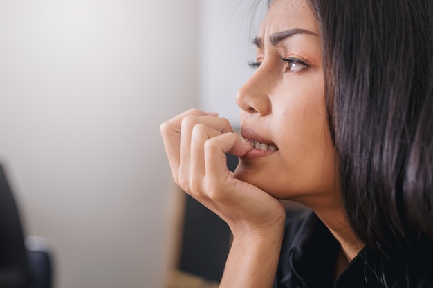 Nervöse geschäftsfrau, die ihre nägel mit sorgengefühl im büro beißt.