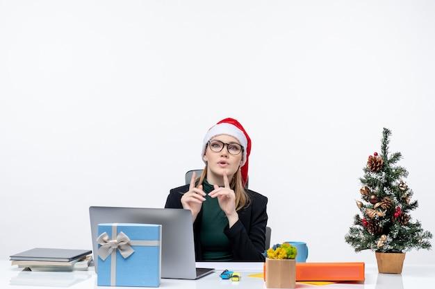 Nervöse geschäftsfrau mit weihnachtsmannhut, der an einem tisch mit einem weihnachtsbaum und einem geschenk darauf im büro auf weißem hintergrund sitzt