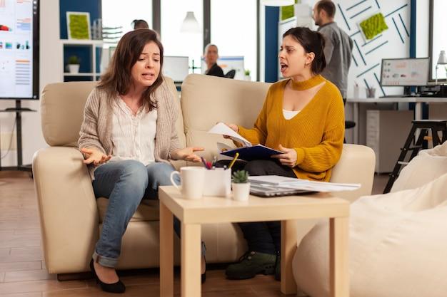 Nervöse geschäftsfrauen mit großen konflikten, streit über fehler aus projektdokumenten