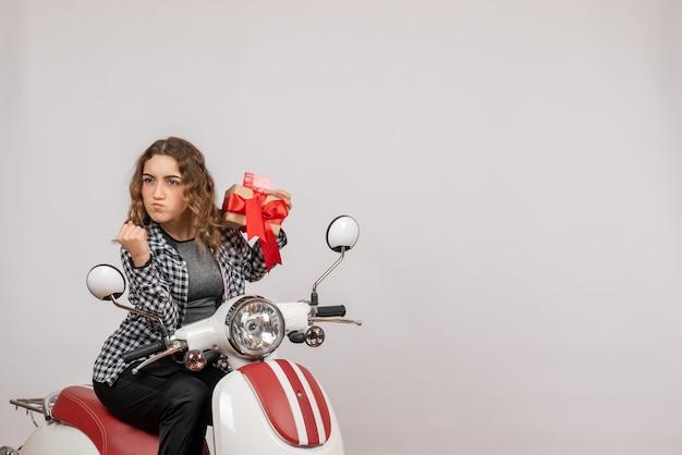 Nervöse junge frau auf moped, die geschenk und karte auf grau hält