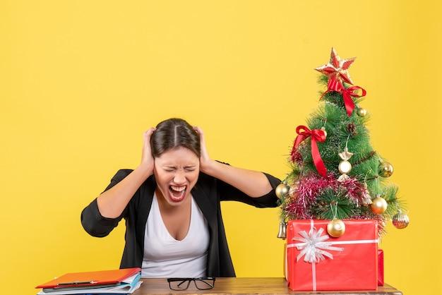 Nervöse junge frau im anzug nahe geschmücktem weihnachtsbaum im büro