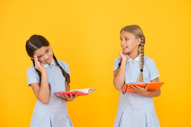 Nervöse kinder. nette kinder, die buch auf gelbem hintergrund lesen. entzückende kleine mädchen lernen, kopienraum zu lesen. lesen und schule zu hause. studiere fleißig. prüfung kommt. abschlussprüfung. schwieriges thema.