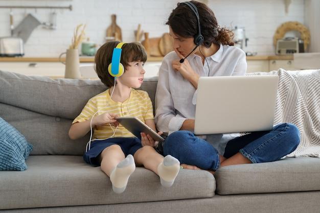 Nervöse mutter sitzt auf der couch zu hause während der sperrung, arbeit am laptop, kind lenkt von der arbeit ab