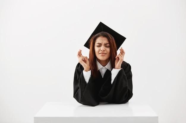 Nervöse studentin, die hofft, ihr diplom zu bekommen, mit gekreuzten fingern über der weißen wand