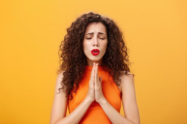 Nervöse und besorgte frau mit lockiger frisur, die hoffnungsvoll mit geschlossenen augen und stirnrunzeln betet ...