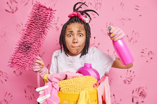 Nervöse, unordentliche hausfrau drückt die lippen, bringt das haus in ordnung, reinigt das zimmer, hält mopp und reinigungsmittel will keine schmutzige wohnung haben sammelt schmutzige wäsche isoliert über rosa wand