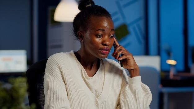 Nervöser afrikanischer manager, der mit mitarbeiter am smartphone diskutiert