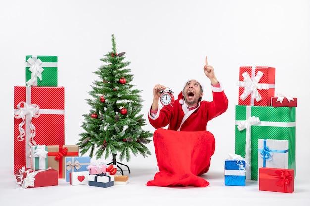 Nervöser aufgeregter weihnachtsmann, der oben zeigt, sitzt auf dem boden und zeigt uhr nahe geschenken und geschmücktem weihnachtsbaum auf weißem hintergrund