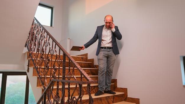 Nervöser büroleiter, der auf dem smartphone spricht, das auf der treppe in der finanzgesellschaft steht, die überstunden macht. gruppe professioneller erfolgreicher geschäftsleute, die in einem modernen finanzgebäude arbeiten.