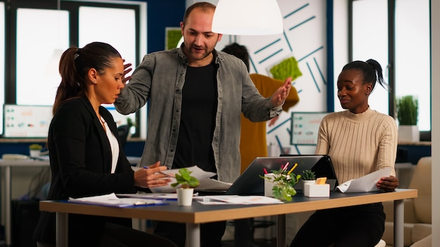 Nervöser geschäftsmann, der sich im coworking space streitet und konflikte am arbeitsplatz hat, beschuldigt schlechte arbeitsinkompetenzfehler. verweis auf erfolglose ergebnisse und rivalitätskonzept.