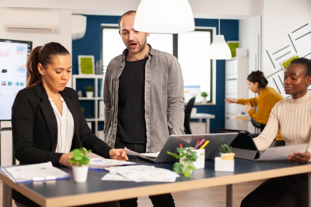 Nervöser geschäftsmann, der sich im coworking space streitet und konflikte am arbeitsplatz hat, beschuldigt schlechte arbeitsinkompetenzfehler