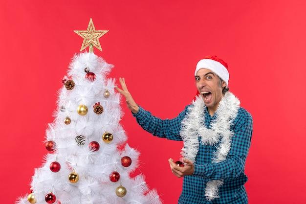 Nervöser junger mann mit weihnachtsmannhut in einem blauen gestreiften hemd und verzierungsweihnachtsbaum auf rot