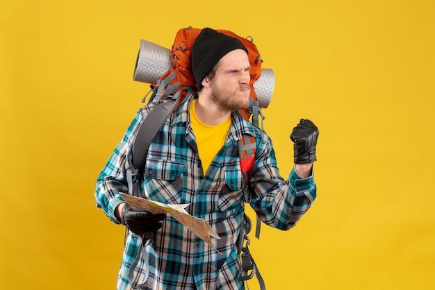 Nervöser junger rucksacktourist mit schwarzem hut, der die karte zum kampf bereit hält