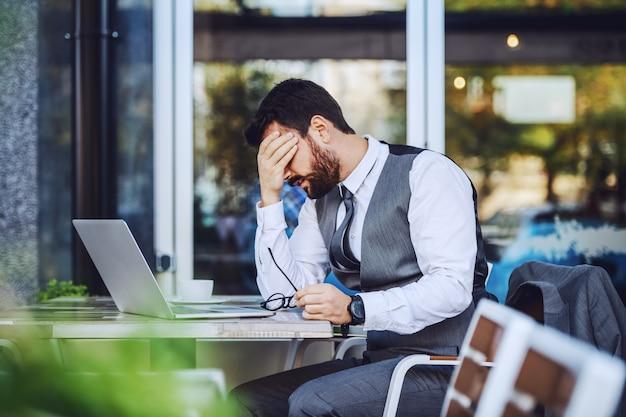Nervöser kaukasischer hübscher bärtiger geschäftsmann im anzug, der im café sitzt und kopf hält. auf dem tisch stehen laptop, kaffee und brille. probleme bei der arbeit.