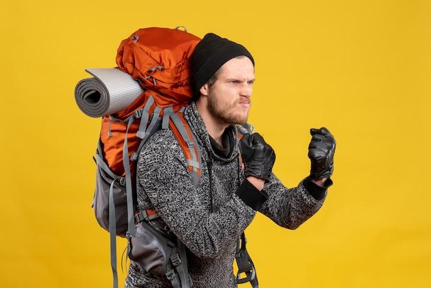 Nervöser männlicher tramper mit lederhandschuhen und rucksack, der bereit ist zu kämpfen