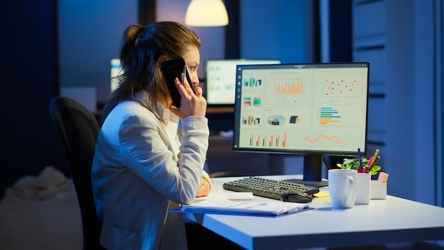 Nervöser manager, der am smartphone mit mitarbeitern diskutiert, die überstunden am schreibtisch im geschäftsbüro spät nachts sitzen, um finanzielle probleme zu lösen. vielbeschäftigter mitarbeiter mit modernem technologienetzwerk
