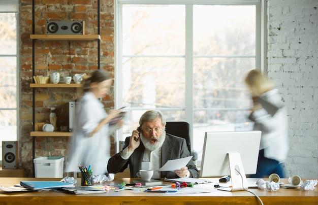 Nervöser und müder chef an seinem arbeitsplatz beschäftigt, während leute, die sich nähern, verschwimmen. büroangestellter, manager, hat probleme und fristen, seine kollegen lenken ab. business-, work-, workload-konzept.