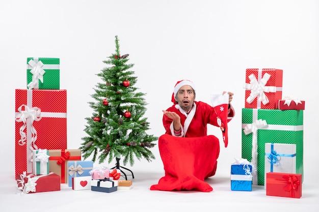 Nervöser weihnachtsmann, der etwas hinterfragt, das auf dem boden sitzt und weihnachtssocke nahe geschenken und geschmücktem neujahrsbaum auf weißem hintergrund hält